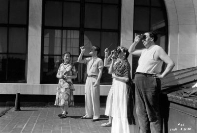 photographer unknown - Frida Kahlo and Diego Rivera, with colleagues, viewing a solar eclipse from the DIA roof, 1932