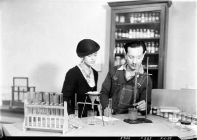 photographer unknown - Frida Kahlo looks on as Andres Sanchez Flores tests pigments for Diego Rivera's Detroit Industry murals at the DIA, 1933